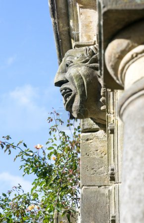 Old gargoyle with ugly open mouth