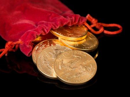 Photo pour Empilements d'aigle d'or une once troy pièces d'or de la Monnaie du Trésor américain versant de la bouche de sac d'argent en velours rouge - image libre de droit
