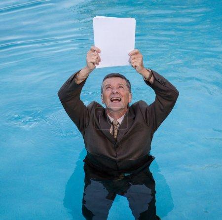 Senior man holding blank paperwork in water