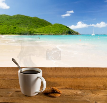 Photo for Morning cup of coffee on a wooden picnic table on Anse Marcel beach on St Martin in Caribbean in idyllic dreamlike location - Royalty Free Image