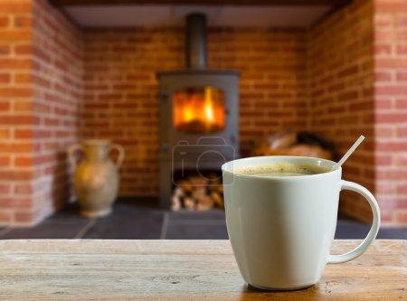 Photo pour Tasse à café sur une table en bois en face de la cheminée à l'intérieur de chauffage au bois poêle dans la cheminée en brique - image libre de droit
