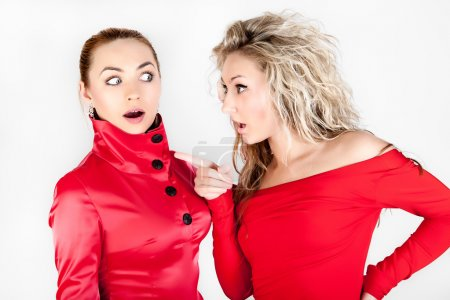 Blonde girl whispering to a friend against white background.