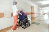 Zdravotní sestra s starší pacient na vozíku