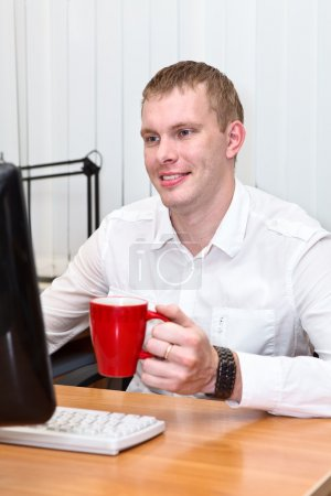 Young white collar worker with red mug in hand at working place
