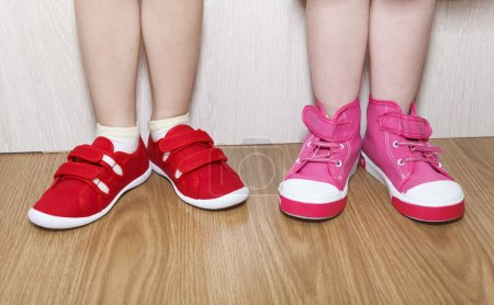 Children in wrong feet and right feet shoes wearing on legs