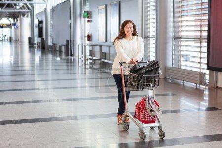Photo pour Jeune femme caucasienne tirant bagages main-charrette avec sacs le long de la salle de l'aéroport. voyageurs en zone d'attente. - image libre de droit