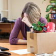 Dismissal at work, weeping employee with things to...