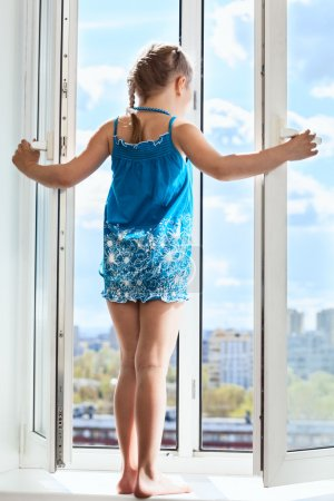 Photo for Young girl standing on window with opened door, looking from height - Royalty Free Image