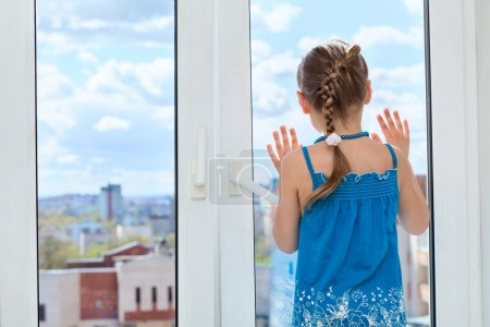 Child looking through window