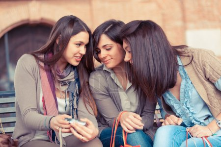 Three Women Looking Photos in the Camera