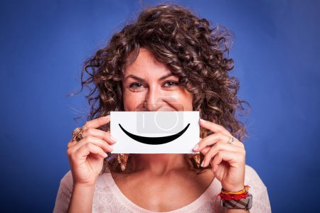 Photo for Young Woman with Smiley Emoticon on Blue Background - Royalty Free Image