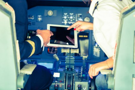 Pilot and Copilot Checking Flight Information on Digital Tablet