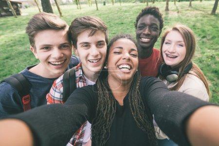Photo pour Groupe d'adolescents multiethniques prenant un selfie - image libre de droit