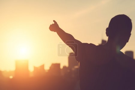 Man aiming at sunset