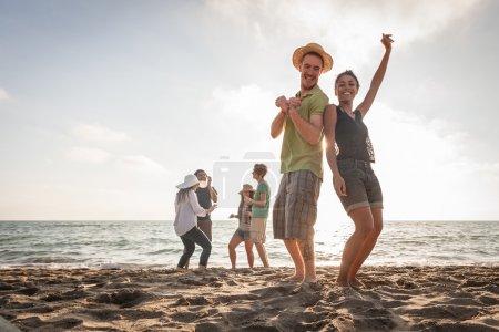 groupe multiracial d'amis ayant une partie à la plage