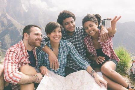 Photo pour Des amis prennent du selfie au sommet de la montagne - image libre de droit