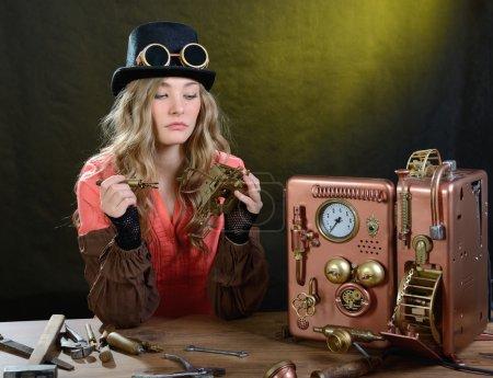 Photo pour Steam punk fille réparer téléphone. Téléphone - Modèle fait main . - image libre de droit