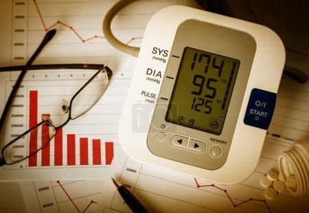 Photo pour Je travaille tard au bureau. Tensiomètre numérique, lunettes, stylo et pilules sur les rapports financiers . - image libre de droit