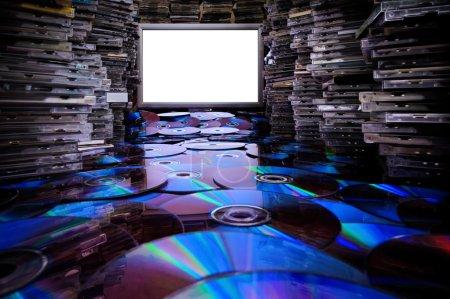 Photo pour Arrêtez de copier illégalement ! D'énormes piles CD original, DVD et leurs copies faites sur l'ordinateur. Moniteur avec espace de copie . - image libre de droit