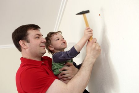 Father and son with hammer