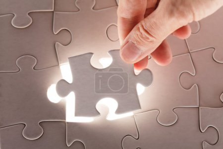 Photo for Hand holding puzzle piece - Royalty Free Image