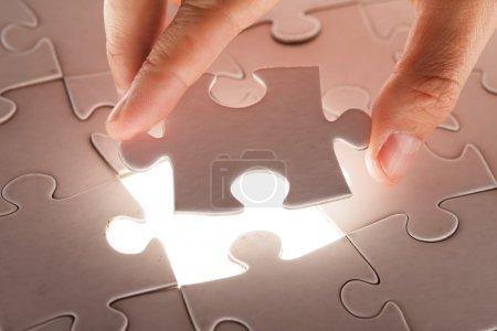 Pièce de puzzle main tenant
