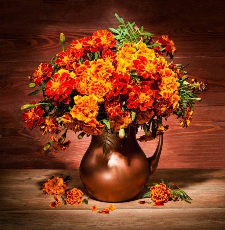 Photo pour Nature morte avec des fleurs d'automne sur une table dans un vase en cuivre - image libre de droit
