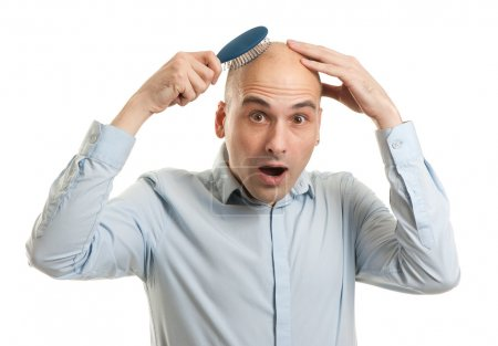 Shocked bald man holding comb