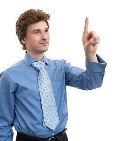 Photo pour Un homme d'affaires pointe du doigt ou appuie sur un bouton imaginaire. Isolé sur fond blanc - image libre de droit