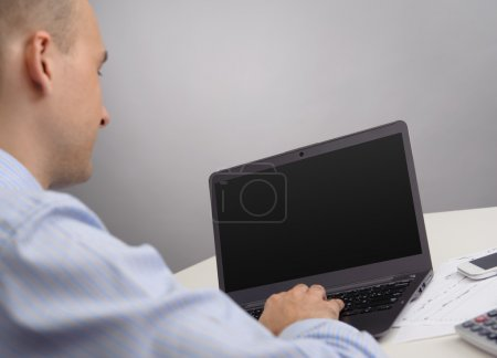 Photo for Rear view of a businessman with laptop computer - Royalty Free Image