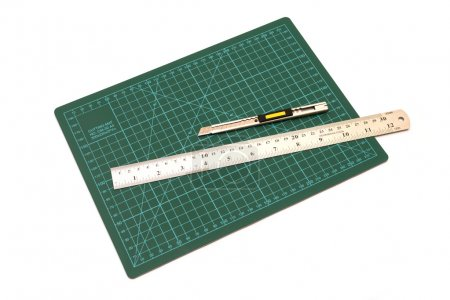 Green cutting mats with iron ruler and cuter isolated on white b