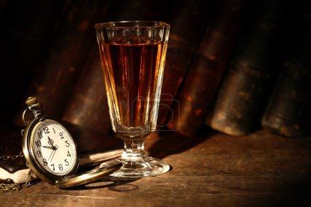 Photo pour Vintage petit verre à vin avec de l'alcool près de la montre de poche ouverte sur fond avec de vieux livres - image libre de droit
