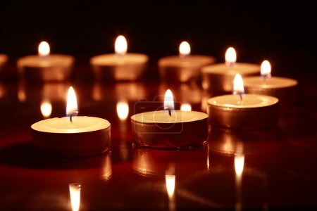 Photo for Set of lighting candles in a row on dark background - Royalty Free Image