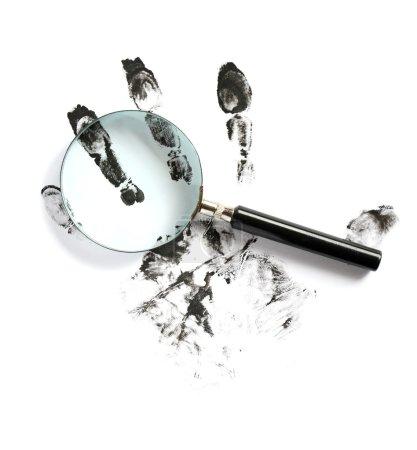 Photo pour Concept de crime. Empreintes digitales noires et loupe sur fond blanc - image libre de droit