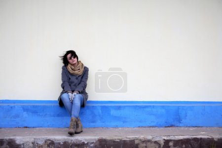 Photo for Beautiful young girl sitting against yellow wall - Royalty Free Image