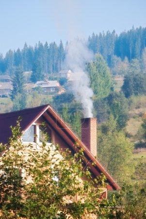 Photo pour La fumée de la cheminée de la maison dans le village - image libre de droit