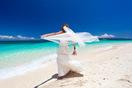 Happy dancing bride on beach