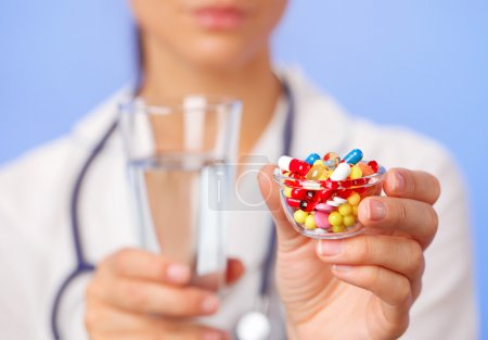 Pills, tablets and drugs heap in doctor hand, closeup view
