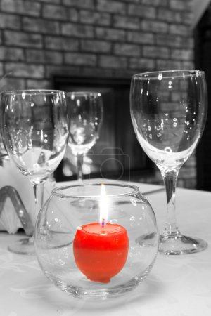 Burning candle on the served table against a fireplace