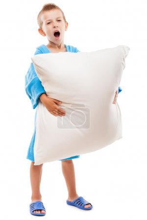 Yawning child boy holding pillow going to sleep