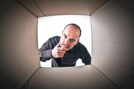 Photo for Caucasian man look into a cardboard parcel - Royalty Free Image