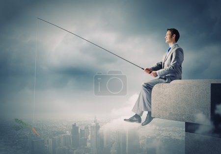 Businessman fishing with rod