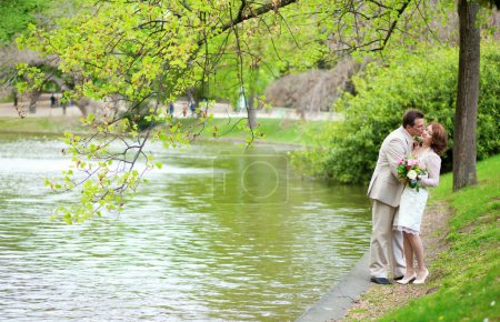 Happy just married couple hugging and kissing near the lake in p
