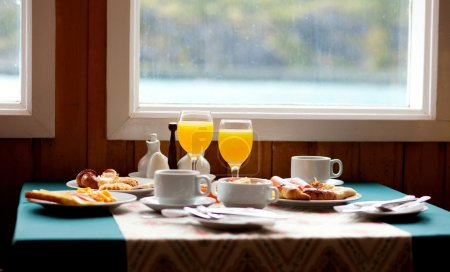 Delicious breakfast served on a table near the window at rainy d