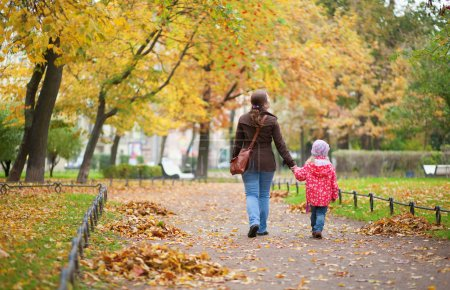 Mother and daughter walking together at beautiful autumn day
