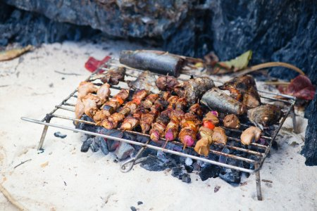 Meet and fresh fish grilled on a beach