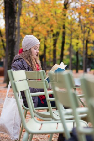 Girl reading a book in an outdoor cafe