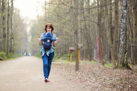 Photo pour Jeune mère marchant en forêt avec son bébé en porte-bébé - image libre de droit