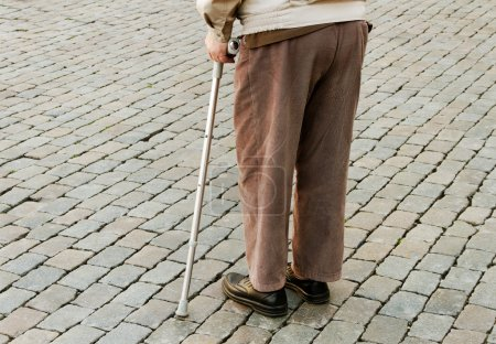 Photo for Old man with crutch on a street. - Royalty Free Image