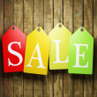Colorful sale tags hanging on wooden background...